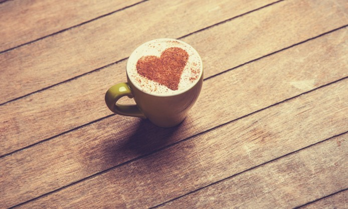 cappuchino-coffee-heart-green-mug-wooden-texture-694x417